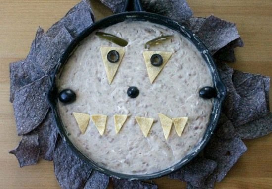 Bean dip garnished to look like a monster for a Halloween party appetizer