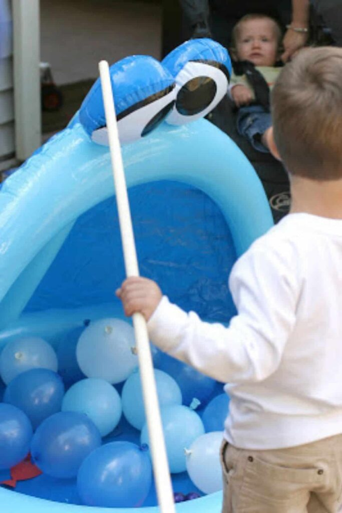 toddler playing a party game in an inflatable pool filled with balloons