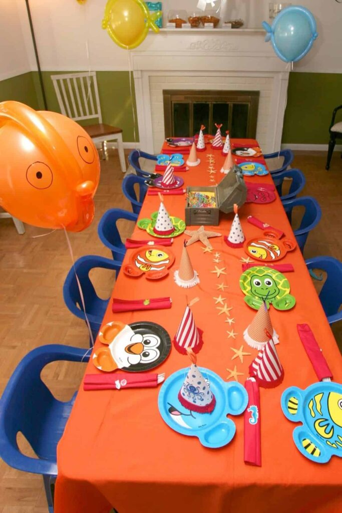 overhead view of a birthday party table for kids with an orange tablecloth and blue chairs