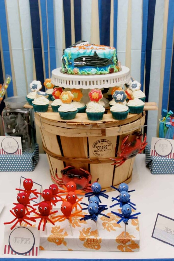 under the sea dessert and favor table with crepe paper backdrop and crab pot holding up a cake