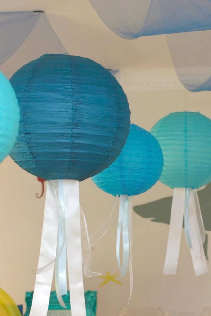 paper lanterns hanging from a ceiling with ribbons to look like jellyfish tentacles