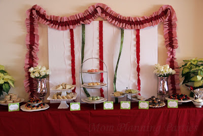Weet treats buffet with ribbon backdrop framed by pink and red ruffle garland