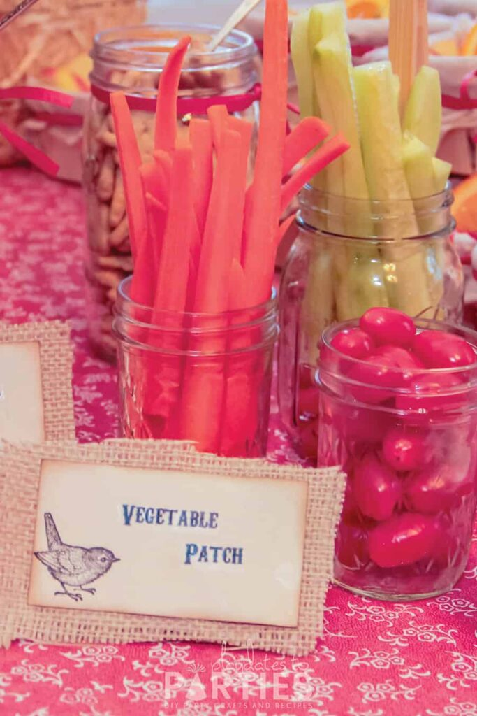 mason and jelly jars filled with vegetables with a rustic buffet label in front that says Vegetable patch