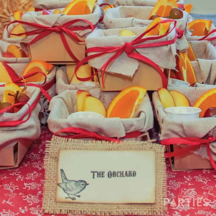 Wood berry baskets filled with fruit with a rustic buffet label that says The Orchard