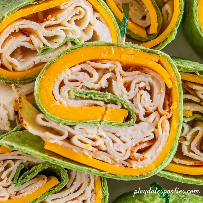 A very close image of chicken cheddar pinwheel sandwiches showing the layering of the ingredients
