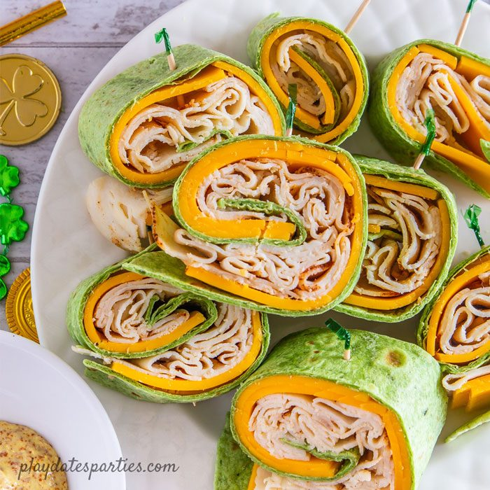 a plate full of chicken cheddar pinwheel sandwiches with St. Patrick's Day decorations next to it and mustard on the side