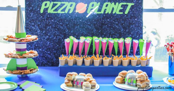 Pizza planet party buffet with rocket ship tray purple and green cones and UFO platters