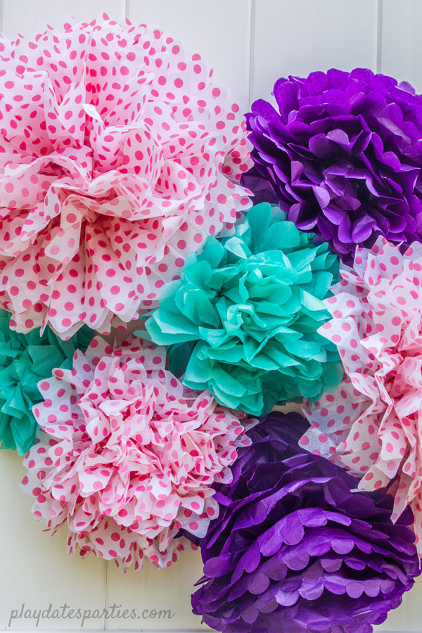 Several brightly colored tissue paper pom poms in a bunch