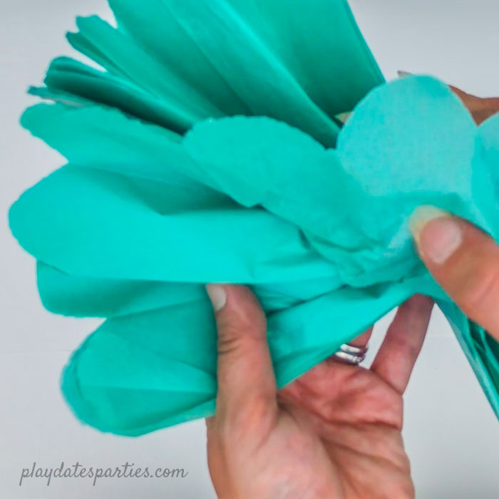 Opening the pom pom from the center and not the edges