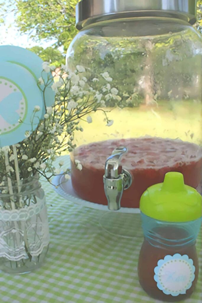glass punch pitcher on a table with a vase of baby's breath and a sippy cup in front