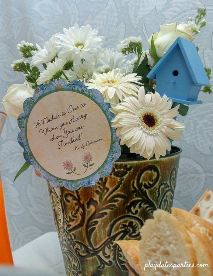 "White flowers in a green vase with blue accents, and a card with the quote ""A Mother is One to whom you hurry when you are troubled"" by Emily Dickenson"