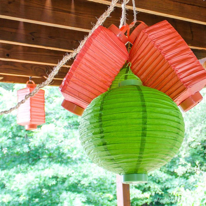 A chandelier made with battery-operated lanterns in orange and green.