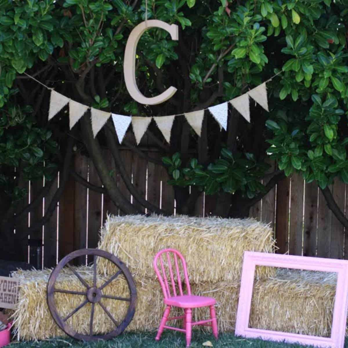 Photo booth setup with hay bales, a pink picture frame, a wagon wheel, and burlap bunting hanging from the tree above