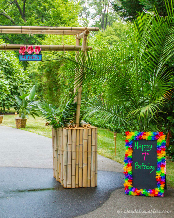 The entrance to a luau party, with a tiki arch, palm trees, and a happy birthday sign bordered in colorful Hawaiian leis.