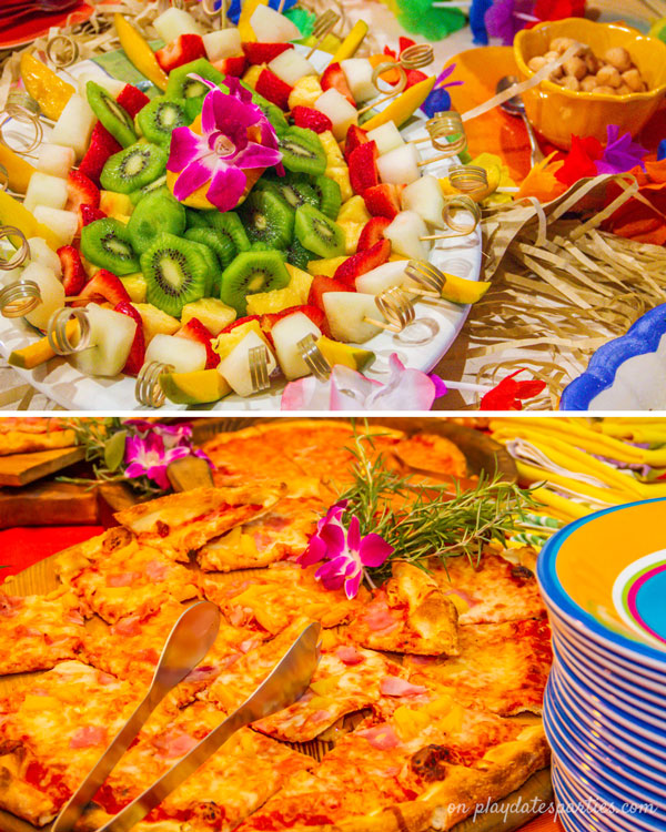 Luau party food for kids, including pizza, fresh fruit skewers and macadamia nuts