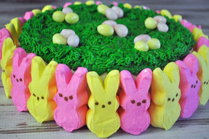 Easter Peeps cake with peeps around the edges and grass piped on top