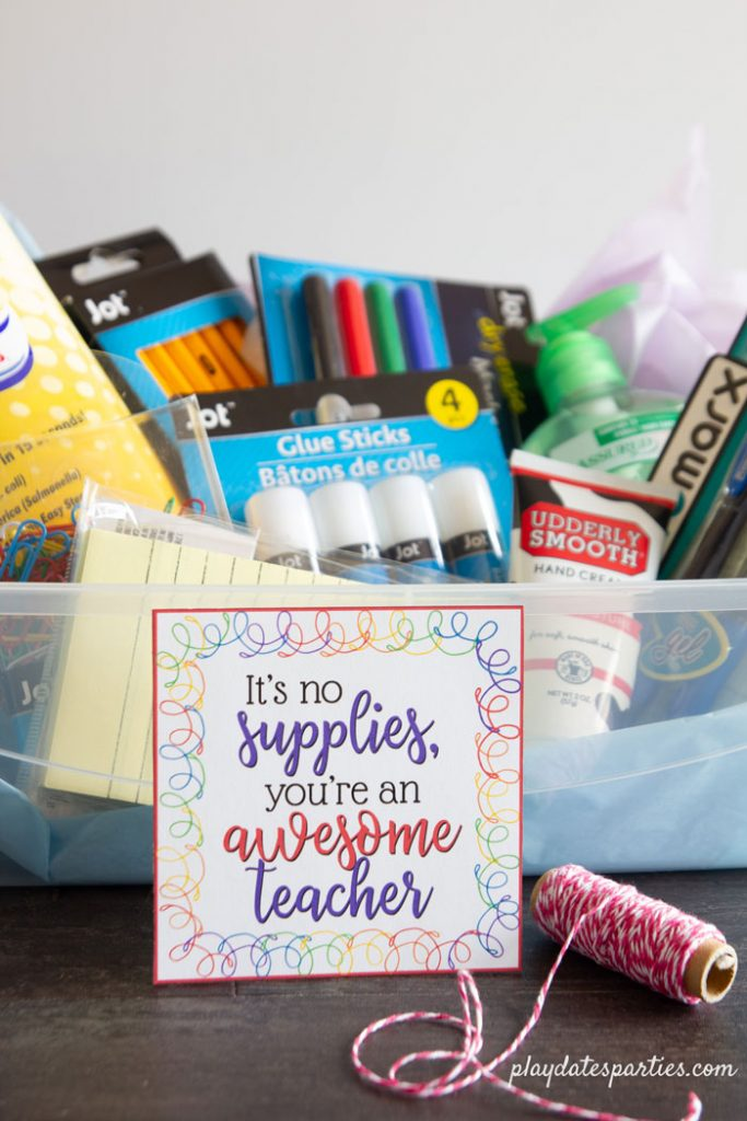 A photo of school supplies in a box with a teacher appreciation tag that say it's no supplies you're an awesome teacher.