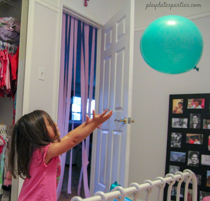 A toddler playing with a balloon on her birthday with a streamer-covered door in the background.