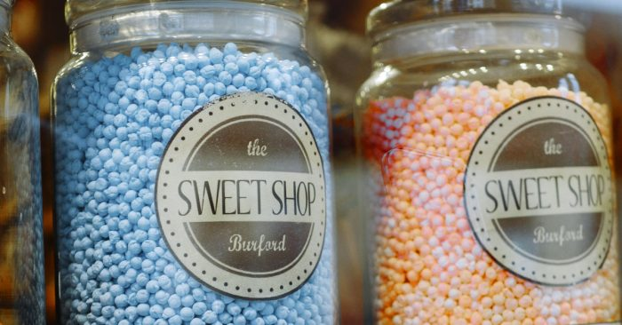 Pink and blue candies in sweet shop jars