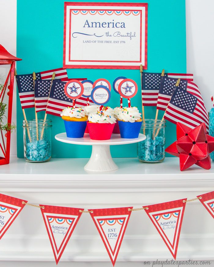 A picture of the full set of Independence Day printables displayed on a mantel with American flags