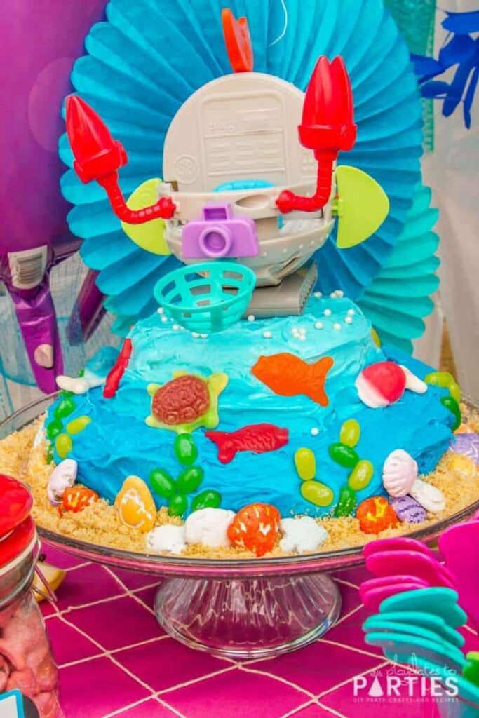 Octonauts party cake with ombre blue frosting, jelly bean seaweed, gummy fish, and chocolate seashells