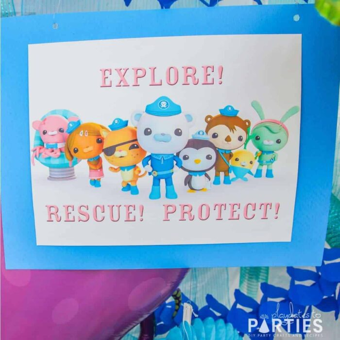 close up image of a printed sign with Octonauts team and the words Explore! Rescue! Protect!