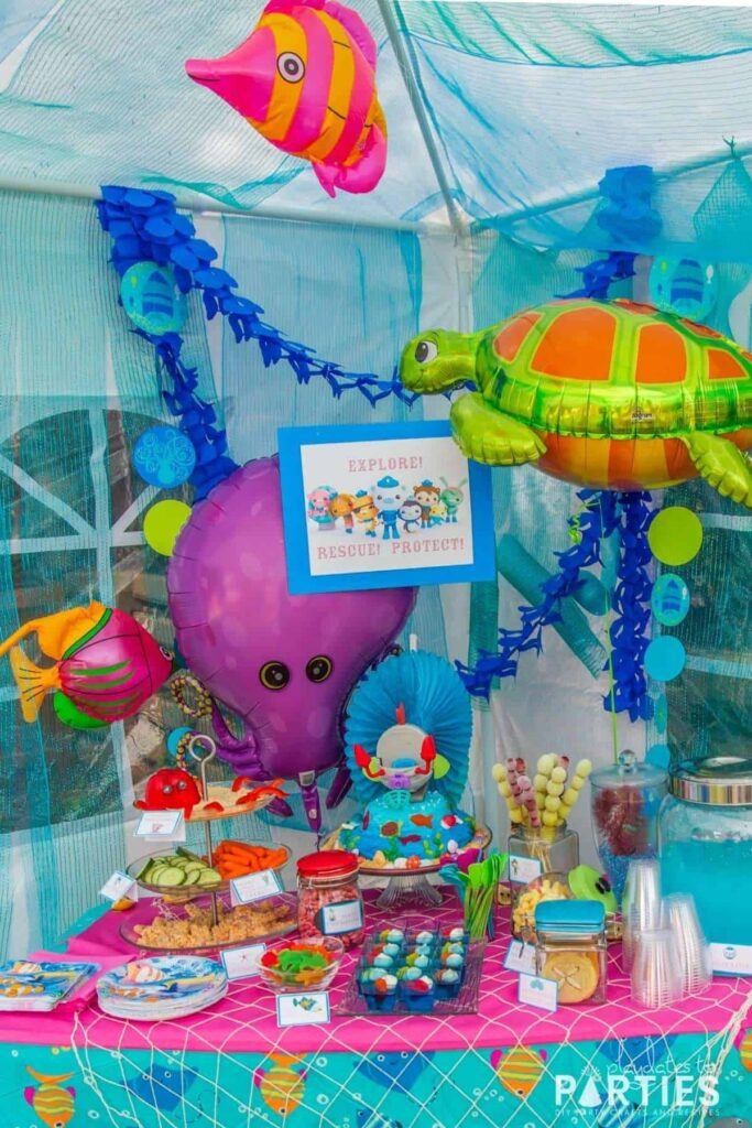 Octonauts party snack table with sea creature balloons, blue streamers, and a party sign
