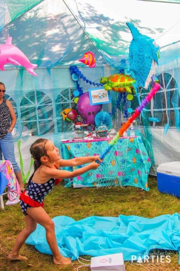 a little girl hitting a shark pinata inside a party tent