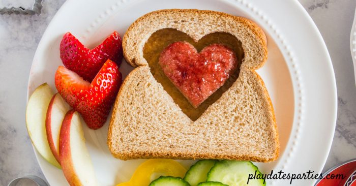 Peanut butter and jelly sandwich with a heart in the center, jelly side up