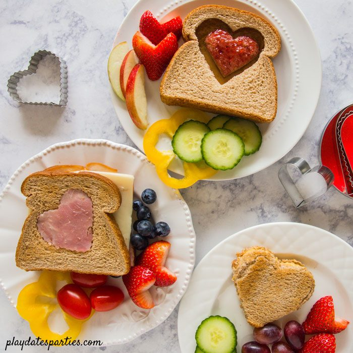 three versions of heart shaped sandwiches with fruit and vegetables