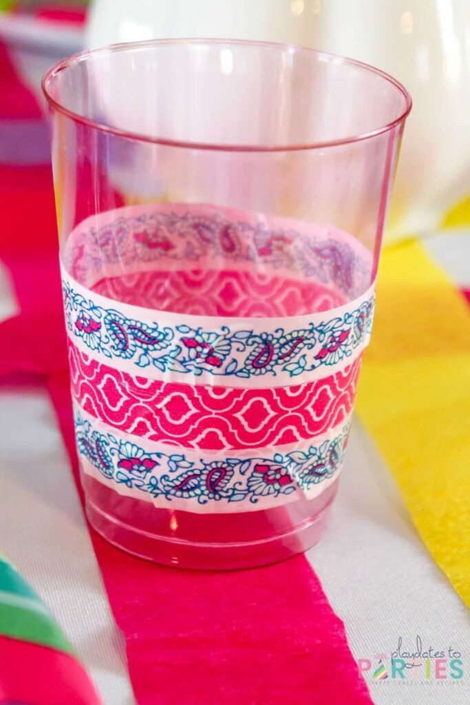 a pink tinted clear plastic cup wrapped with blue and pink washi tape on a table decorated with crepe paper streamers