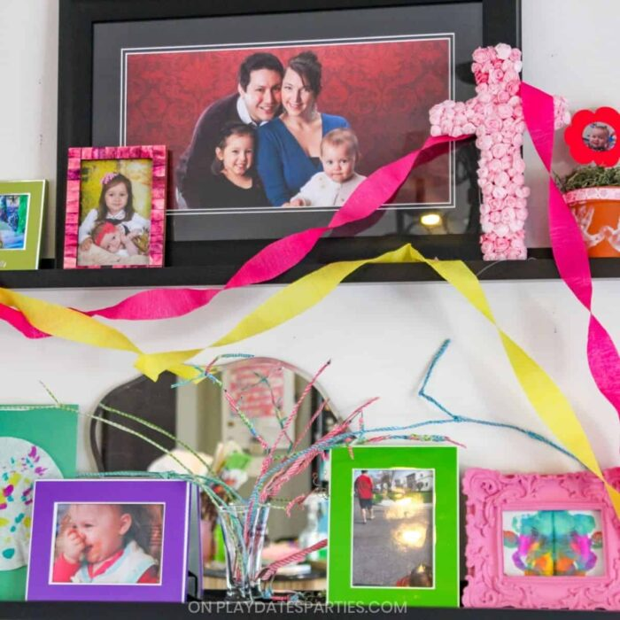 two wall ledges filled with colorful frames that have family photos and kids artwork
