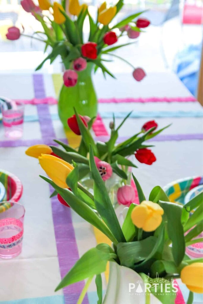 Close up of 3 vases filled with tulips as centerpieces for a kids Easter table