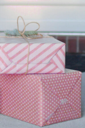 Two gifts wrapped in pink wrapping paper on a front porch