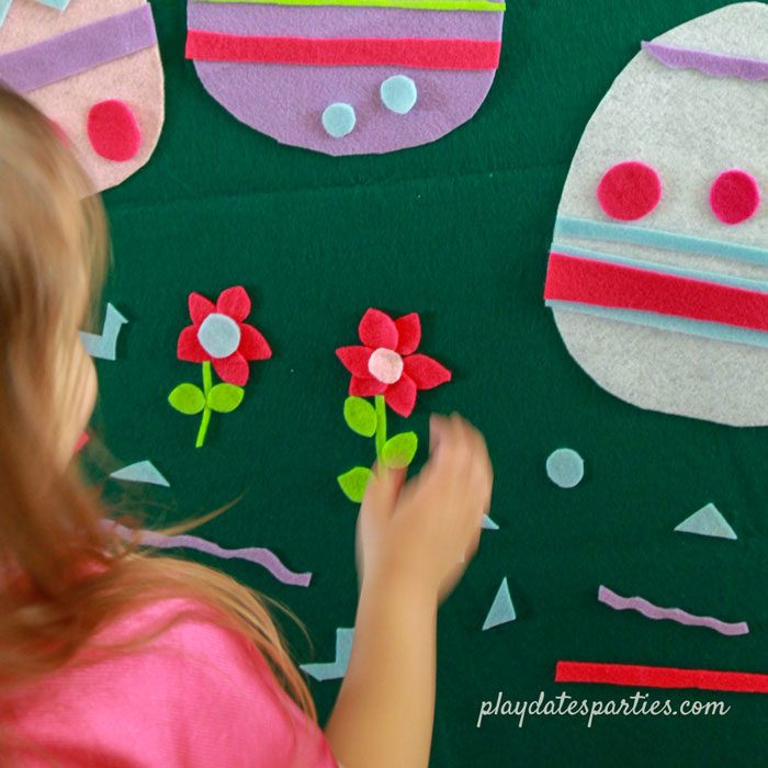 A little girl combining felt shapes to create flowers on a green felt board