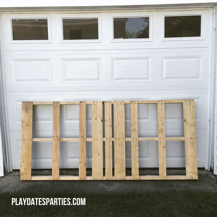 A large unfinished pallet against a garage door.