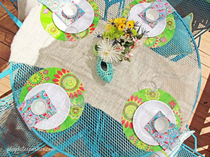Picture of a bright blue painted patio set with place settings and a white burlap table runner.