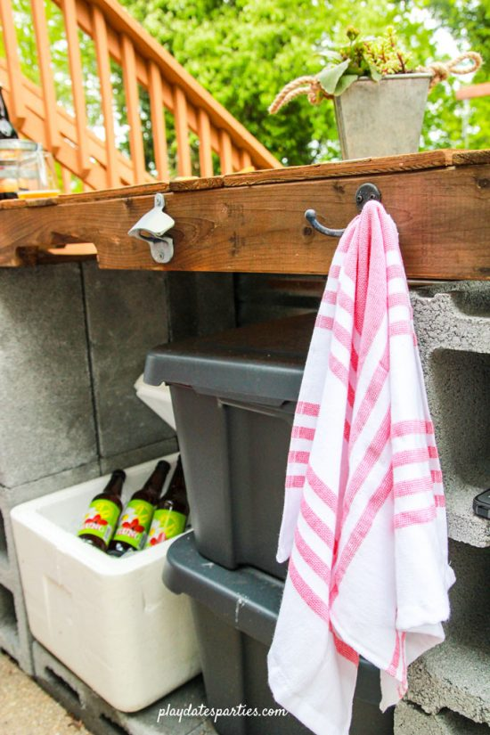 DIY outdoor bar showing a bottle opener, cooler, and towel hooks.