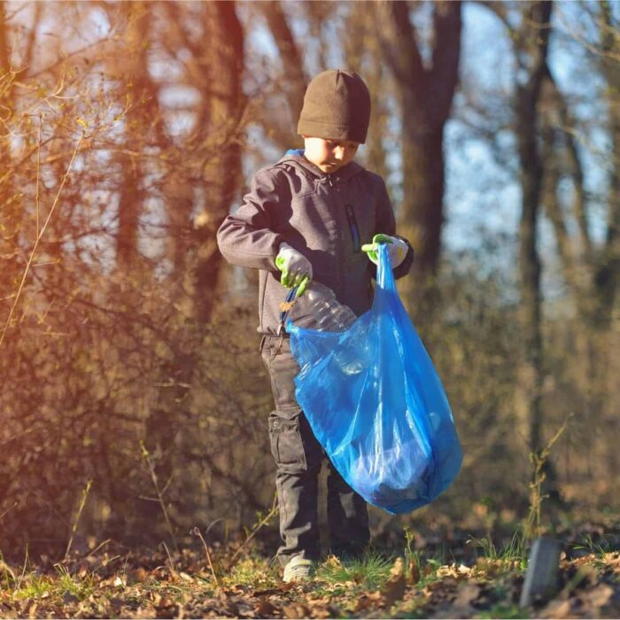 a child picking up litter outdoors