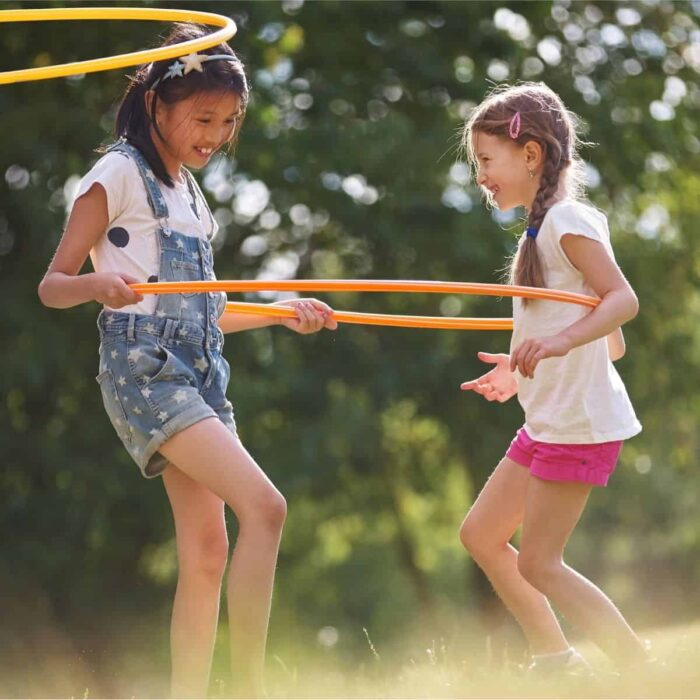 two girls playing outside with a hula hoop