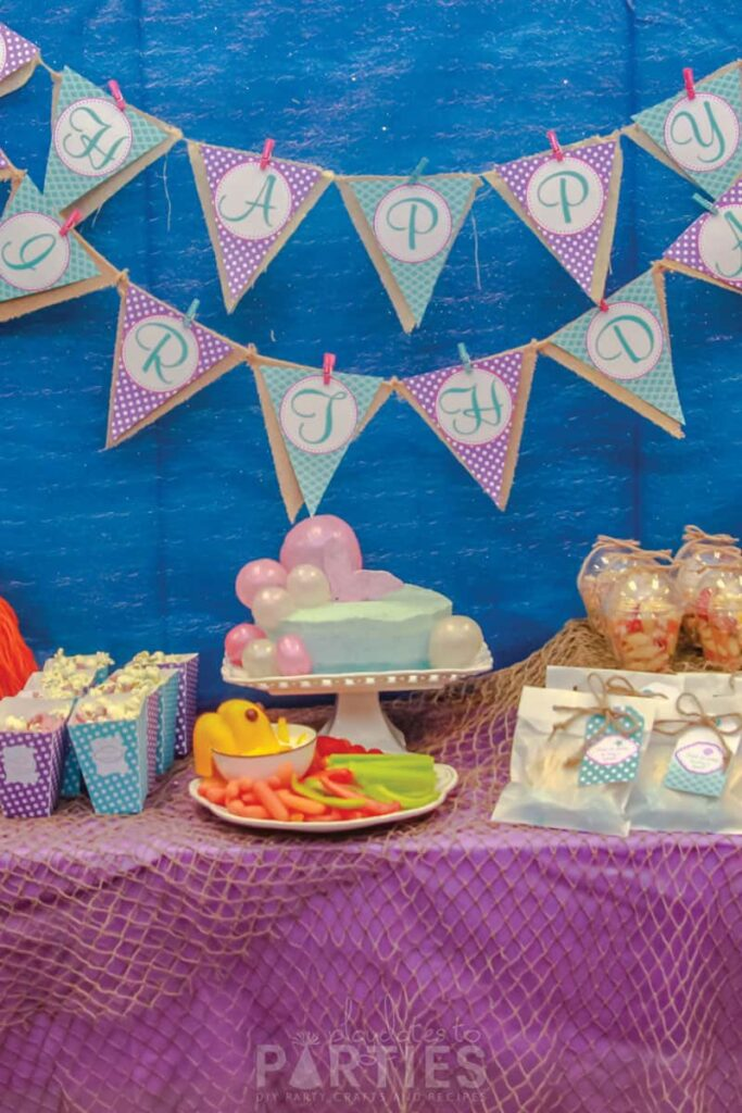 Blue pink and purple birthday party with fish netting and a layered banner