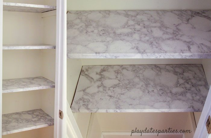A look at linen closet shelves after applying faux marble contact paper for shelves.