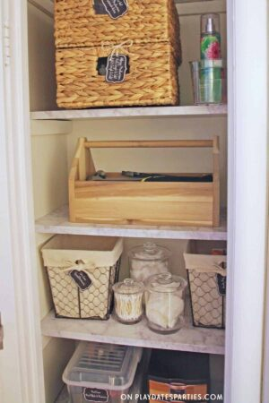 photo of an organized linen closet with baskets, jars, and boxes that are all labeled with farmhouse style chalkboard labels