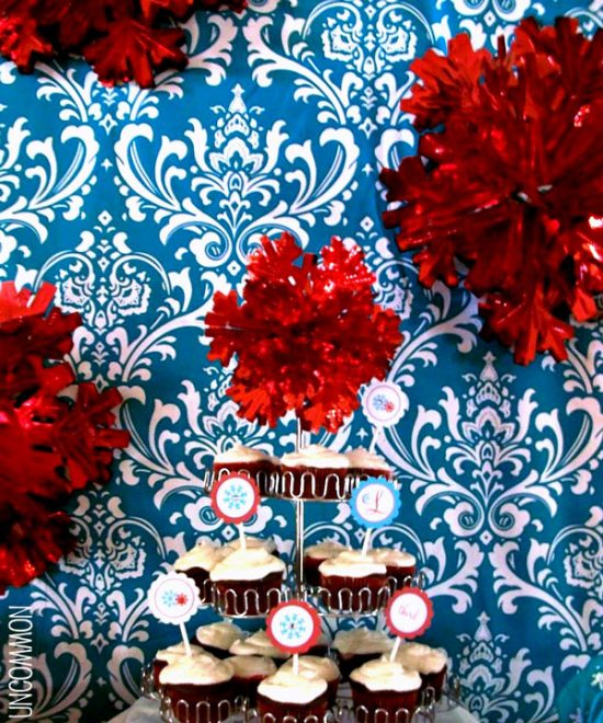 Winter wonderland birthday party with a blue damask backdrop and fluffy red snowflake decorations