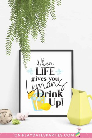 art print in a black frame that says when life gives you lemons drink up with a yellow pitcher and other decor around it