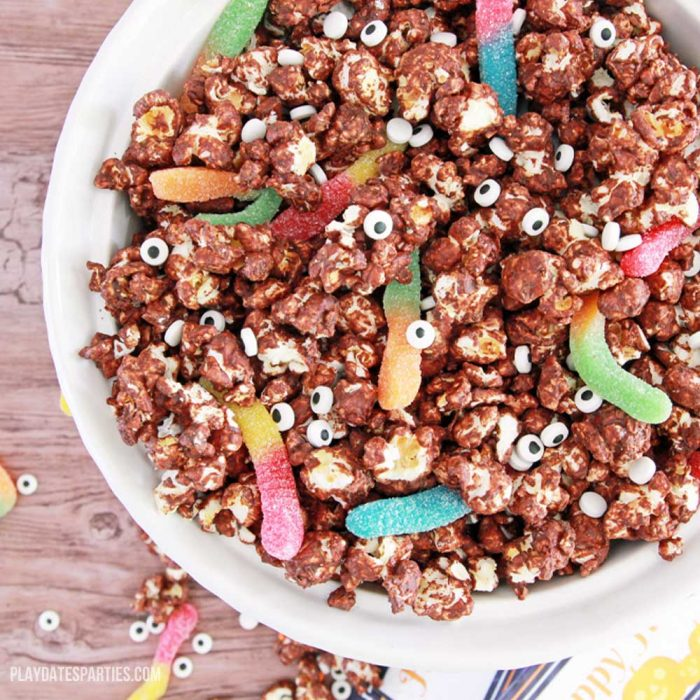 Chocolate coated Popcorn mix in a bowl with gummy worms and candy eyes