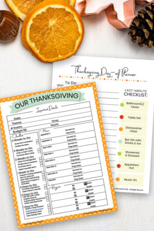 Thanksgiving dinner planner printables on a table with orange slices & pine cones
