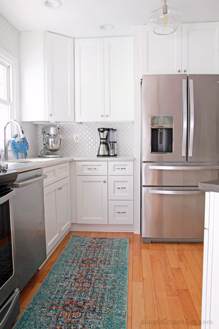 Big style can fit in #small spaces! Take a look at how this small white kitchen renovation turned a broken-down #kitchen into an updated, bright, and classic room. This home #design includes faux marble quartz countertops, DIY wood shelves, light wood floors, and modern white tile.