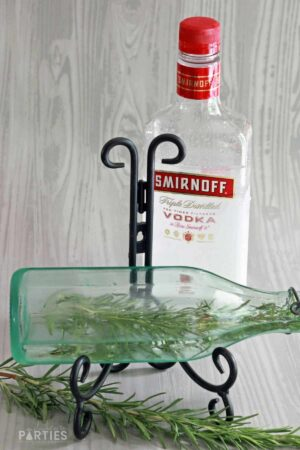 a bottle of vodka behind a partially filled bottle with a rosemary sprig inside