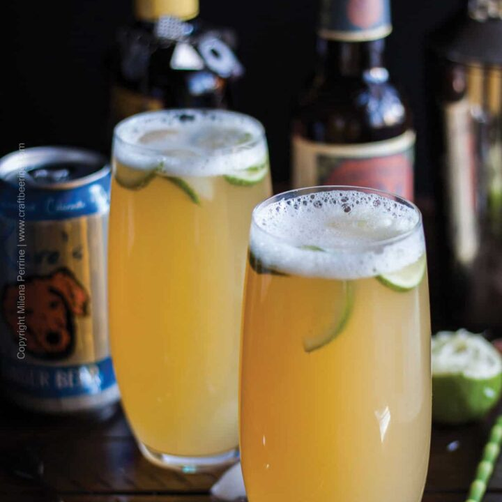 two beer cocktails garnished with lime in front of bottles of IPA